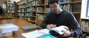 A man reads an open book in a library