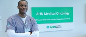 A man in medical wear stands in front of a Medical Oncology sign