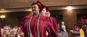 A row of Bidwell Training Center graduates walk down an isle