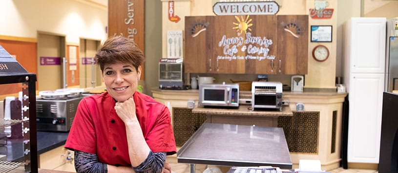 A Bidwell Training Center Alumna smiles, she is working in her business called 'Anna's Sunrise Cafe and Catering'.