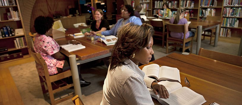 A woman works at a table in a library. Another table behind her is occupied by three students studying.