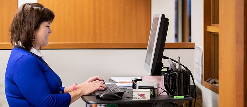 A woman works at a computer inputting important medical data