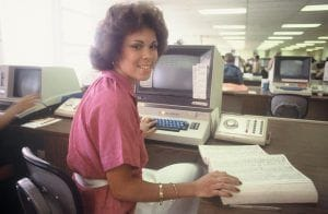 Bidwell Training Center in 1984, a woman sits at a desk with a book and a computer
