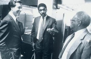 William E. Strickland, Jr. talking with two men in suits
