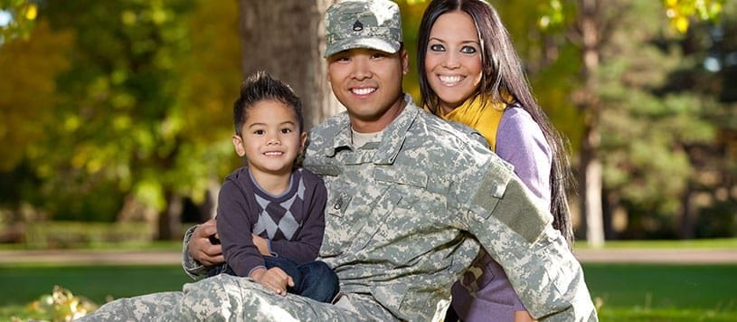 Military and veteran family sits on a lawn together