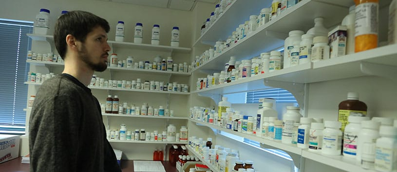 A man looks at a variety of prescription drugs displayed on wall shelves.
